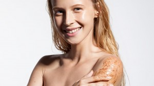 Young woman with scrub cleanses the skin